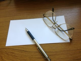 A piece of paper with reading glassess and pen set on a desk