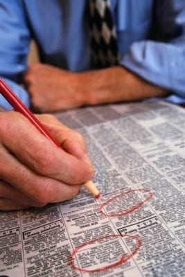 Showing a man holding a red pen and circling job vacancies in a paper