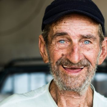 An smiling ageing worker with a cap