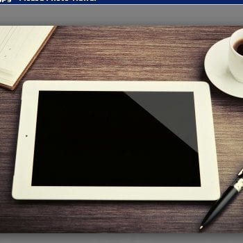 Picture of an ipad with a cup of coffee on a desk and pen and paper