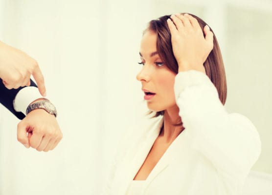 boss showing time to stressed businesswoman