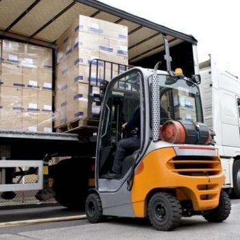 a fork lift truck unloading a lorry at a warehous