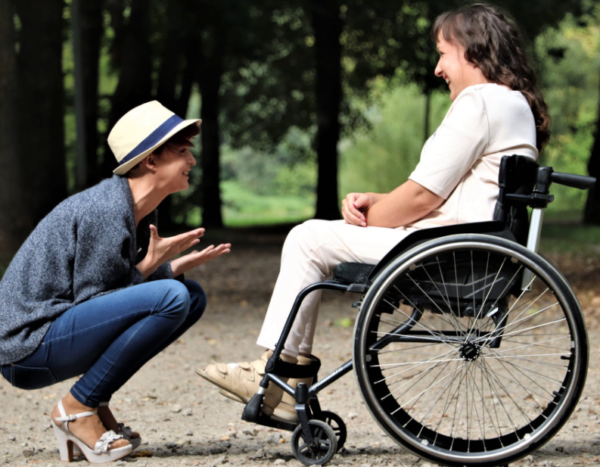 a woman in a wheelchair talking to another