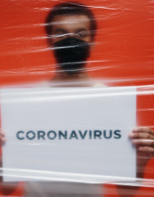 man holding a card with coronavirus written on it